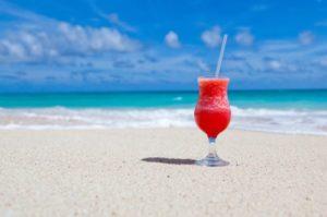 Kühler roter Drink an weißem Sandstrand