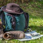 """Rucksach, Wanderschuhe und Hut im Gras als Symbol für unsere Aktivität """"Wandern"""""""