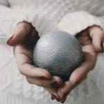 Boulekugel in den Händen als Symbol für das Boulespielen
